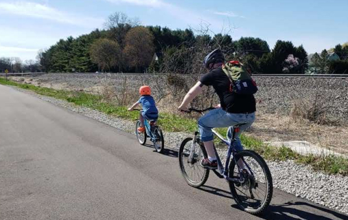 Father and young child riding on the border to border trail